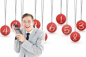 Geeky smiling businessman holding calculator against hanging red three