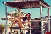 young woman in bikini  sit at shade at seaside beach enjoy in summer hot sunny day, full body shot