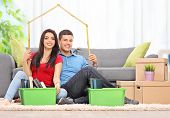 Young couple sitting in a living room and making a roof over their heads with a tape measure at home
