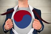 Businessman opening shirt to reveal korea republic flag against bleached wooden planks background