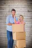 Attractive young couple leaning on boxes with piggy bank against wooden planks background