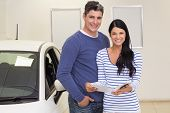Smiling couple holding a booklet while looking at camera at new car showroom