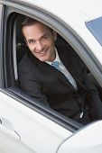 Handsome businessman smiling at camera in his car