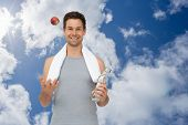 Smiling fit young man with apple and water bottle against bright blue sky with clouds