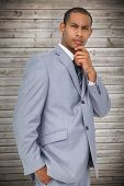 Thinking businessman against wooden planks background