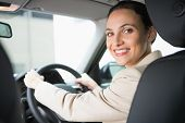 Pretty businesswoman smiling and driving in her car