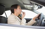 Businesswoman using mirror to put on lipstick while driving in her car