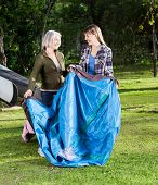 stock photo of tent  - Happy mother and daughter making tent in park at campsite - JPG