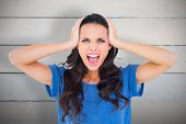 Angry brunette shouting at camera against painted blue wooden planks