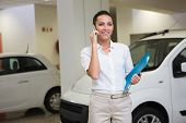 Smiling businesswoman on the phone holding folder at new car showroom