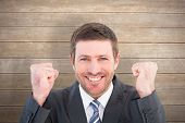 Businessman smiling and cheering against wooden surface with planks