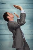 Businessman standing with arms pressing up against wooden planks