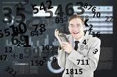Geeky smiling businessman holding calculator against business interface with graphs and data