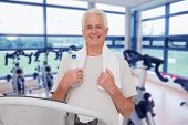 Senior man on the treadmill against spinning exercise bikes in gym room