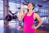Fit woman taking a drink against spin bikes in fitness studio