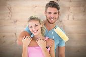 Young couple hugging and holding paint roller against bleached wooden planks background
