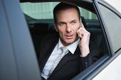 Serious businessman using his phone in his car
