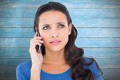 Pretty brunette talking on the phone against wooden planks