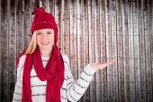Festive blonde presenting with hand against wooden planks