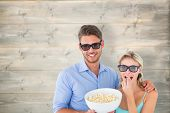 Happy young couple wearing 3d glasses eating popcorn against bleached wooden planks background