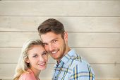 Attractive couple smiling at camera against bleached wooden planks background