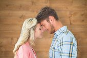Attractive couple standing touching heads against bleached wooden planks background