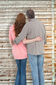 Casual couple standing arms around against faded pine wooden planks