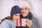 Happy couple in warm clothing holding mugs against wooden background in purple