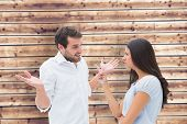 Angry brunette accusing her boyfriend against wooden planks background