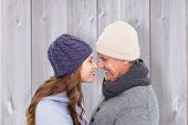Couple in warm clothing facing each other against wooden background