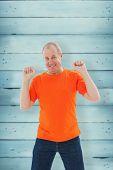 Mature man in orange tshirt cheering against wooden planks