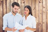 Attractive young couple reading their bills against wooden planks