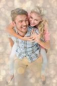 Handsome man giving piggy back to his girlfriend against light glowing dots design pattern