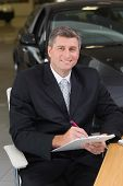 Businessman sitting at his desk while writing on clipboard at new car showroom