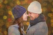 Couple in warm clothing facing each other against close up of christmas lights