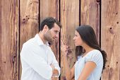 Angry couple facing off during argument against wooden planks background