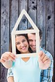 Happy young couple with house shape against grey wooden planks