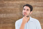 Serious thinking man looking up against wooden planks background