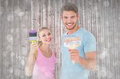 Young couple smiling and holding paintbrushes against grey abstract light spot design