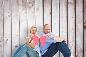 Sad mature couple holding a broken heart against wooden planks