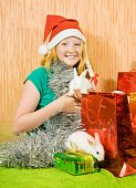 stock photo of tawdry  - teenager girl in new year decoration with two pet rabbits - JPG