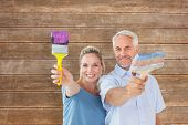 Happy couple holding paintbrushes smiling at camera against wooden planks background