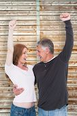 Casual couple cheering and smiling against wooden background in pale wood