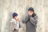 Sick mature couple blowing their noses against pale wooden planks