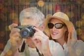 Vacationing couple taking photo against close up of christmas lights