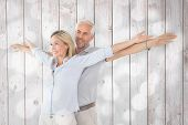 Happy couple standing with arms outstretched against light circles on grey background