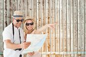 Happy tourist couple using map and pointing against faded pine wooden planks