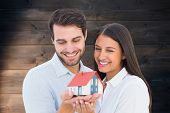 Attractive young couple holding a model house against wooden planks background