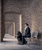 Young woman sitting on a bench with your best four-legged friend