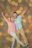 Attractive couple smiling and cheering against close up of christmas lights